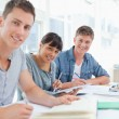 Stockfoto: Three students sitting together as they all look into the camera