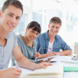 Three students sitting together as they all look into the camera — Stock Photo