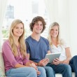 Two sisters and a brother sit on the couch looking at the camera — Stock Photo