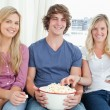 Three friends enjoying popcorn together — Stock Photo