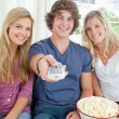 Three friends eating popcorn together as they look at the camera — Stock Photo