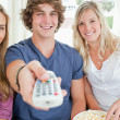 Focus shot on three friends as they use the remote to change the — Stock Photo