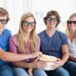 Friends smiling as they eat popcorn and watch a 3d movie — Stock Photo