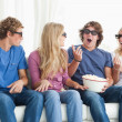 图库照片: Friends laugh and joke around while watching movie