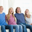 Laughing friends sit on the couch together — Stock Photo