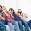 Friends enjoying video games as they all lean to the side — Stock Photo