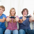 A smiling gang of friends as they look at the camera while gamin - Stock Photo