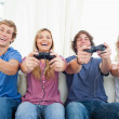 Stock Photo: A group of friends all playing video games together and smiling