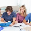 Four smiling students helping each other - Foto Stock