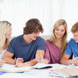 Four students laughing as they work together - Foto Stock