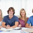 Four smiling students looking into the camera - Foto Stock
