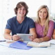 Stock Photo: Couple hold tablet together while looking into camera
