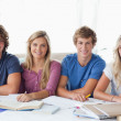 A smiling group of student sitting and looking at the camera — Stock Photo