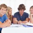 A group of students sitting together as they all study as one si — Stock Photo #10337090
