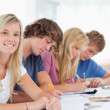 Students working as one girl smiles and looks at the camera - Foto Stock
