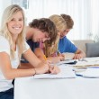 A smiling girl looks at the camera as her friends study — Stock Photo #10337115