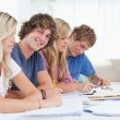 Students studying together with one man looking at the camera an - Stock Photo