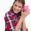 Portrait of a young woman shaking a piggy bank — Stock Photo