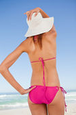 Back view of an attractive teenager in beachwear holding her str — Stock Photo