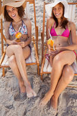 Young women laughing in deck chairs while holding fruit cocktail — Stock Photo