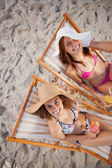 Young women sitting on deck chairs while laughing together — Stock Photo