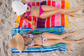 Overhead view of two young women tanning in the sun on the beach — Stock Photo