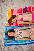 Overhead view of smiling attractive women tanning in the sun — Stock Photo