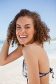 Young woman wearing a bikini while smiling and standing on the b — Stock Photo