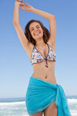 Smiling young woman raising her arms to show her happiness — Stock Photo