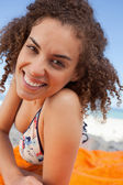 Young smiling woman lying down on a beach towel while staring at — Stock Photo