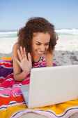Young woman waving her hand in front of her laptop while lying o — Stock Photo