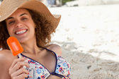 Smiling woman showing a beaming smile while holding an ice looly — Stock Photo
