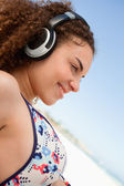 Beautiful young woman in bikini listening to music on the beach — Foto Stock