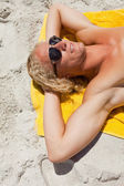 Young blonde man wearing sunglasses while lying on his yellow be — Stock Photo