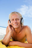 Young blonde man attentively listening to music with his headset — Stock Photo