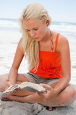 Young blonde woman sitting cross-legged while reading a book — Stock Photo