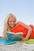 Young smiling woman lying on her beach towel while reading a boo — Stock Photo