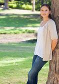 Kvinna i parken lutad mot ett träd — Stockfoto