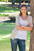 Smiling woman with her arms crossed leaning against a tree — Stock Photo