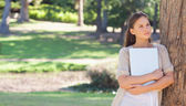 Woman holding a laptop while leaning against a tree — Stock Photo