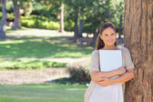 Smiling woman with a laptop leaning against a tree — Stock Photo