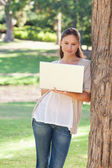 Woman using a laptop while leaning against a tree — 图库照片