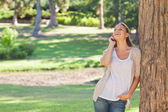 Cheerful woman on the phone leaning against a tree — Stockfoto