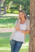 Smiling woman on her cellphone leaning against a tree — Stock Photo