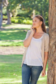 Woman talking on the phone while leaning against a tree — Stock Photo