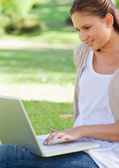 Smiling woman using her laptop while sitting on the lawn — Stock Photo