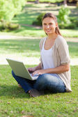 Smiling woman working on her notebook in the park — Stock Photo