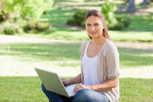 Woman with her laptop sitting on the grass — Stock Photo