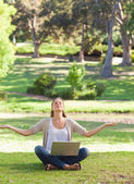 Woman sitting on the lawn in a yoga position with a laptop — Stock Photo