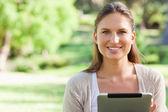 Lachende vrouw die zit op het gazon met een tablet pc — Stockfoto